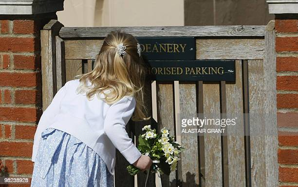 A young girl peaks through a gate as she waits to present a posy to Britain's Queen Elizabeth II after she attended an Easter Sunday church service...