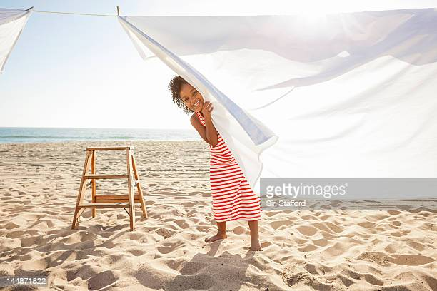 young girl peeking from behind sheet on clotheslin - clothesline stock pictures, royalty-free photos & images