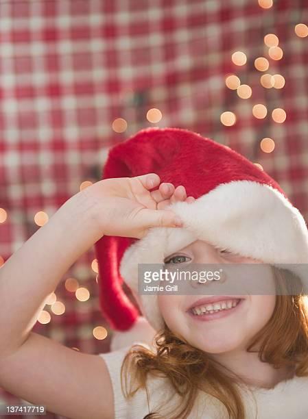Young girl peeking from under Santa hat