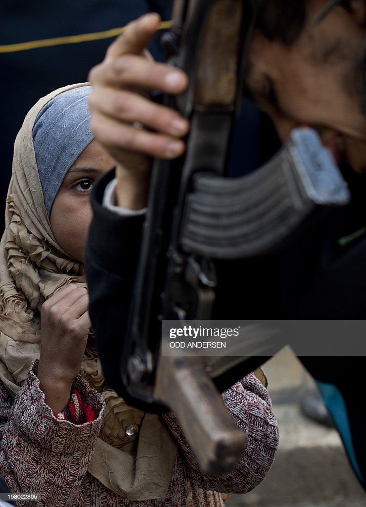 A young girl peeks up at a Syrian opposition fighter monitoring the queue as people line up to buy bread outside a bakery in the al-Fardos neighbourhood of the northern Syrian city of Aleppo on December 9, 2012. The cost of basic commodities such as bread and fuel are rising in the city as Syrians have been struggling to continue their daily lives without water or electricity for one week now.