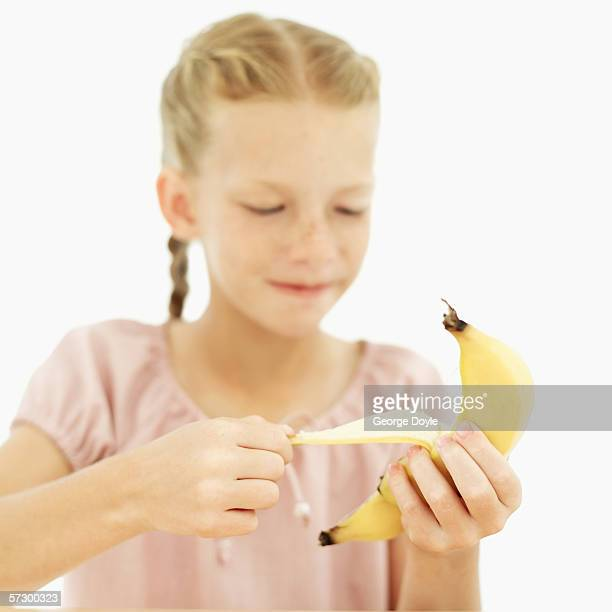 Young girl (10-11) peeling a banana