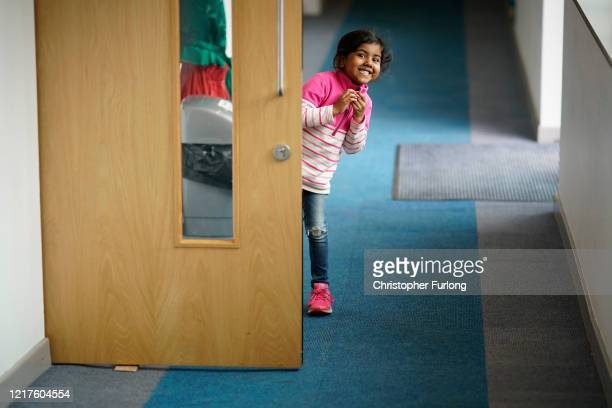 A young girl peeps around the classroom door at the photographer as children of key workers take part in school activities at Oldfield Brow Primary...