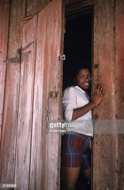 A young girl peers shyly round a halfopen door in New Orleans