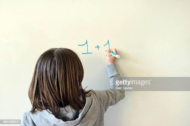 young girl performing arithmetic on a whiteboard - signo de más fotografías e imágenes de stock