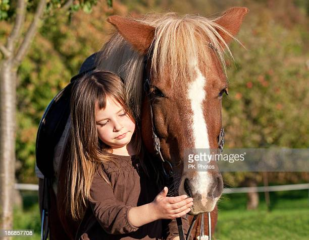 Young girl petting a horse's face