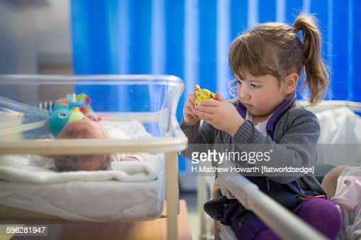 Young girl photographing new born sister