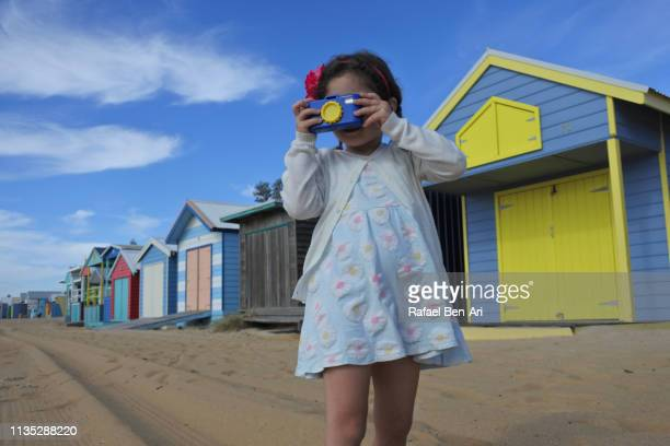 Young girl photographing the Iconic Bathing Boxes of the Mornington Peninsula Victoria Australia