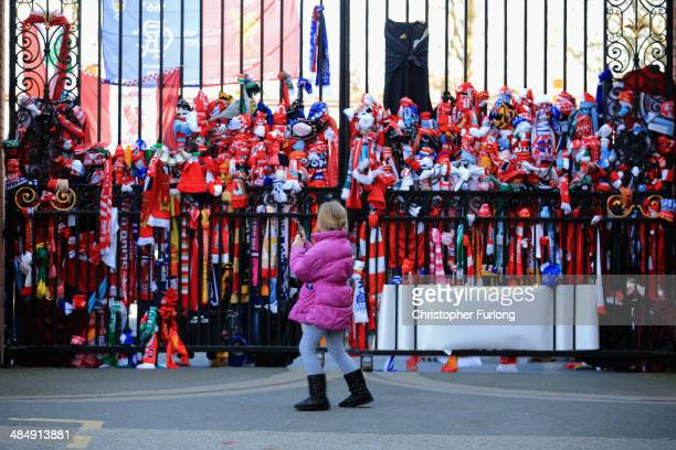 Young girl photographs tributes on the Shankly Gates as fans arrive in Anfield for a memorial service marking the 25th anniversary of the...