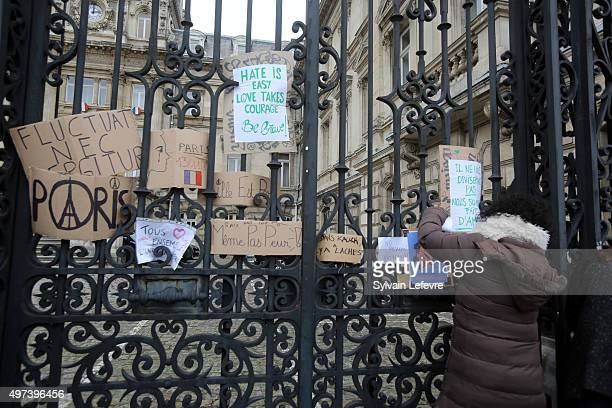 A young girl places a message on the fence of the prefecture after a minute of silence in tribute to the victims of the attacks in Paris on November...