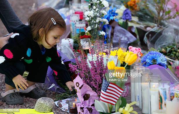 A young girl places a rock on a sign at the makeshift memorial outside of the District Office of US Rep Gabrielle Giffords a day after a gunman...