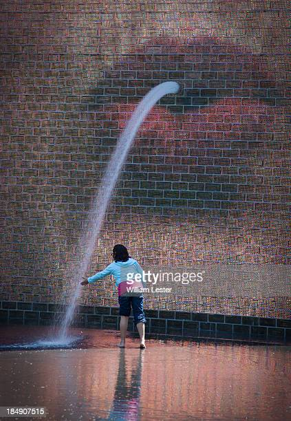 Young girl places her hand in a stream of water coming from the image of pursed at Crown Fountain Millennium Park in Chicago, Illinois, USA