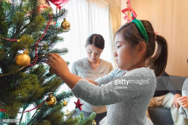 クリスマス ツリーに飾りを置く少女