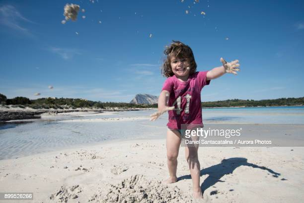 Young girl playing at Cala Brandinchi beach, San Teodoro, Sardinia, Italy