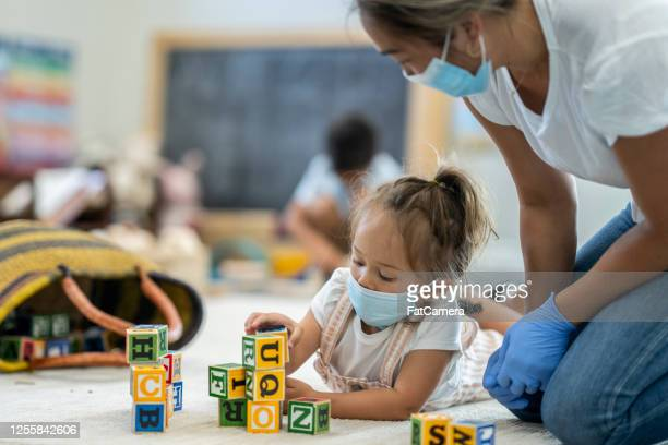 young girl playing at daycare wearing a protective mask - preschool child stock pictures, royalty-free photos & images