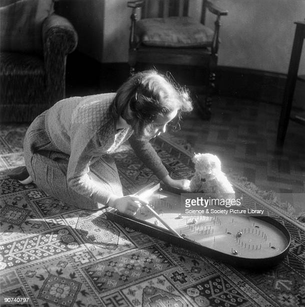 Young girl playing bagatelle c 1930s