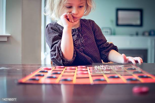 young girl playing checkers game - game board stock photos and pictures