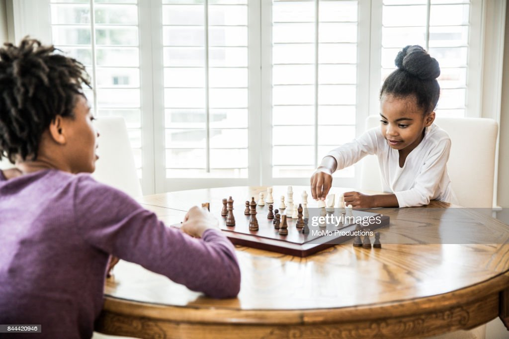 Young girl (6yrs) playing chess with mother : Stock Photo