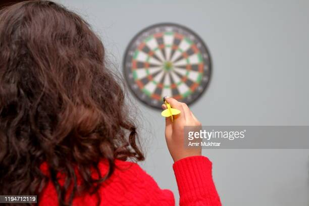young girl playing dartboard game in her room - darts girls stock photos and pictures