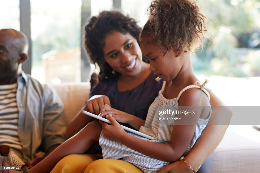 Young girl playing drawing game on digital tablet, with grandmother : Stock Photo