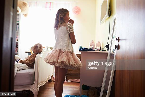 Young Girl Playing Dressing Up Game In Bedroom