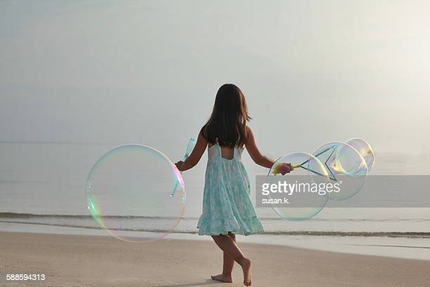 Young girl playing giant bubbles by the beach