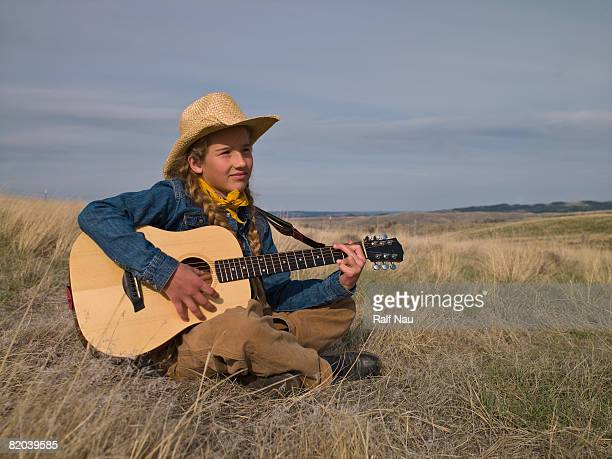 Young girl playing guitar on prairie