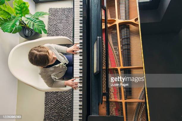 young girl playing her grand piano - ピアノの鍵盤 ストックフォトと画像
