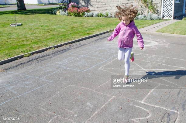 Young girl playing hopscotch in driveway