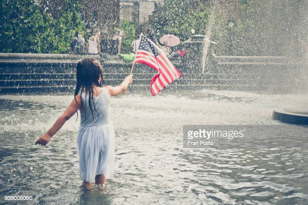 a young girl playing in a park fountain. - happy independence day foto e immagini stock