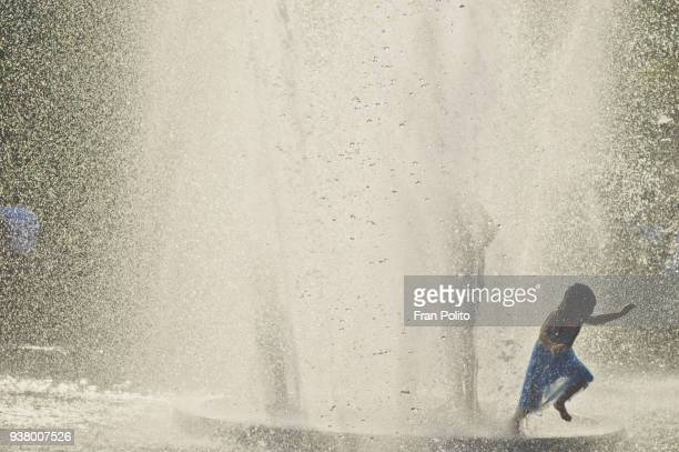 A young girl playing in a park fountain.