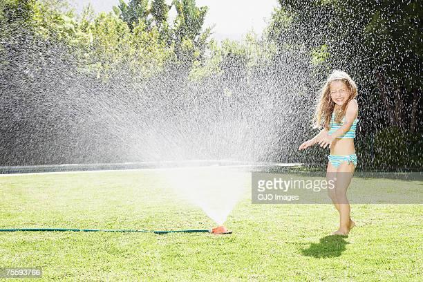 Une jeune fille jouant dans un extincteur automatique