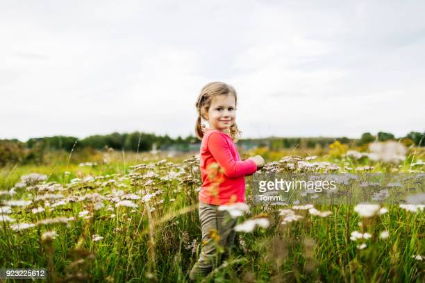 Young Girl Playing In Field Near Family Farm