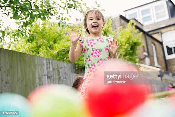 Young girl playing in garden with colored balls
