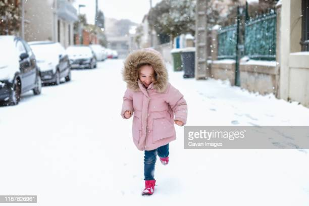young girl playing in street in snow in france facing camera - coat stock pictures, royalty-free photos & images