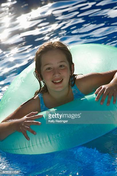 Young girl playing in water inside tube