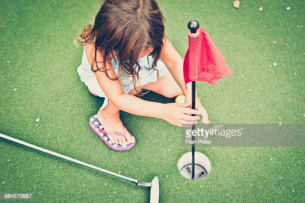 Young girl playing mini golf.