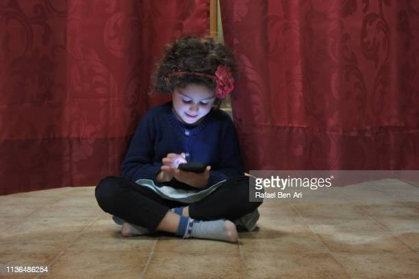 Young girl playing on a smartphone
