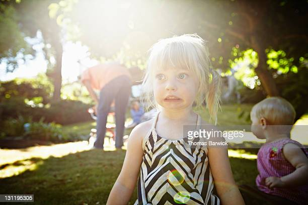 Young girl playing on grass in backyard