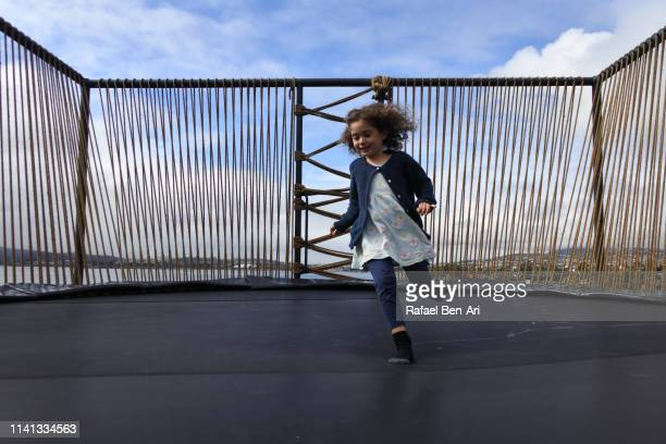 Young girl playing on outdoor trampoline