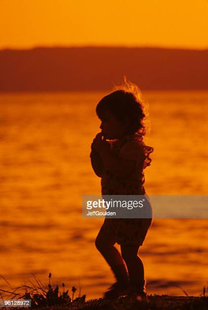 young girl playing on the beach at sunset - jeff goulden stock pictures, royalty-free photos & images
