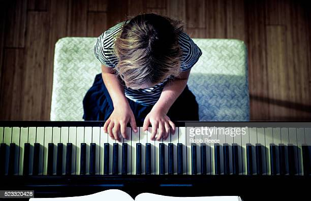 young girl (10-12) playing piano, grand junction, colorado, usa - robb reece stockfoto's en -beelden