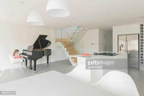 Young Girl playing piano in contemporary home