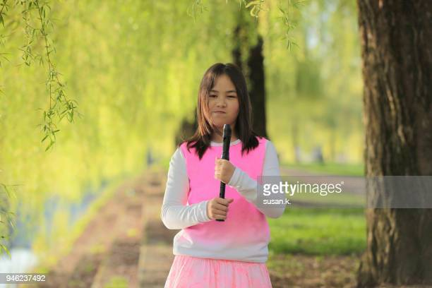 Young girl playing recorder by riverbank.