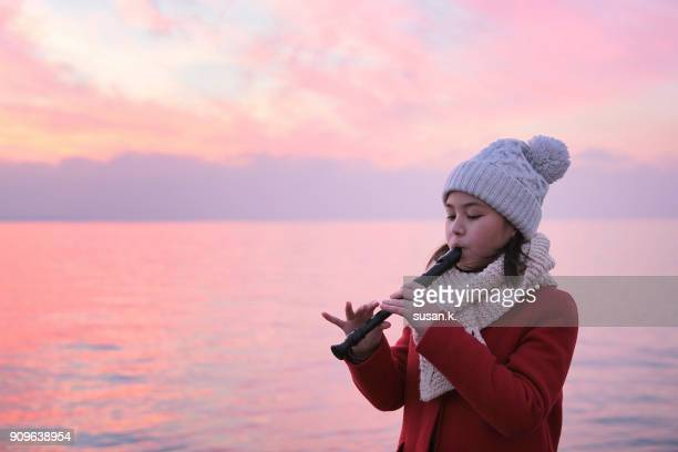 young girl playing recorder by the beach at sunset - recorder musical instrument stock photos and pictures