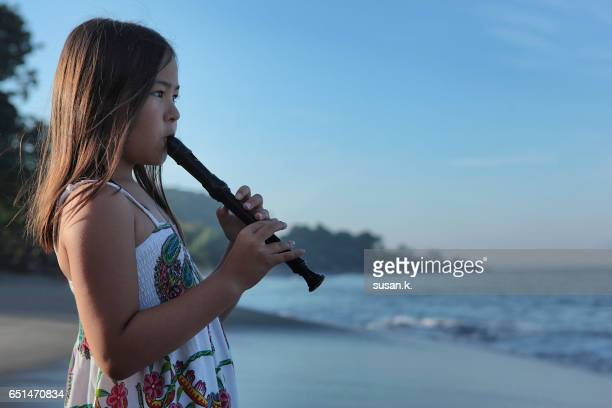 Young girl playing recorder by the beach in the morning