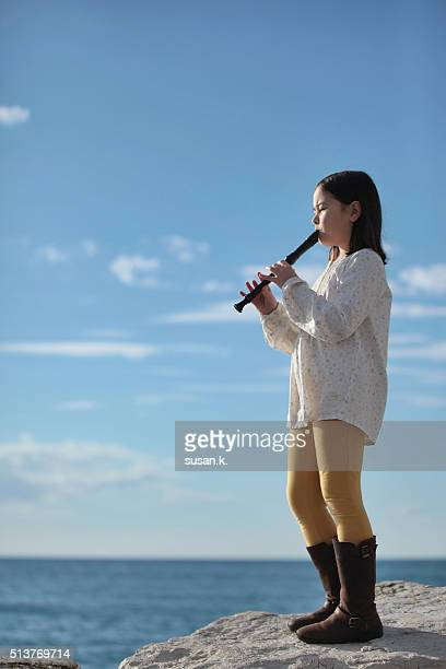 Young girl playing recorder by the sea.