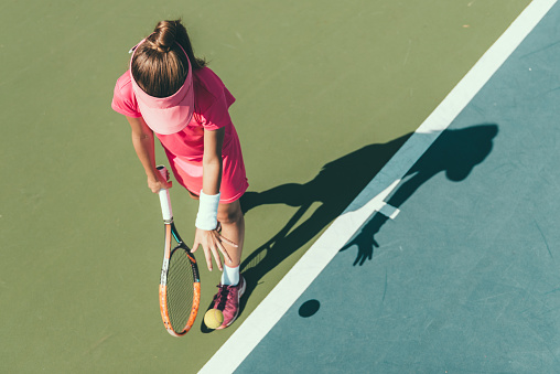 Young girl playing tennis, preparing to serve 814391286