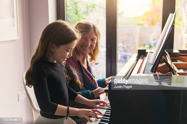 young girl playing the piano with her grandmother - skill stock pictures, royalty-free photos & images