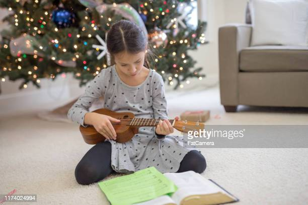 young girl playing ukulule by the christmas tree - ukulele stock pictures, royalty-free photos & images