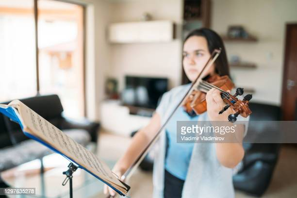 young girl playing violin at home - musician stock pictures, royalty-free photos & images